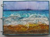 Ring-bound sketchbook with embroidered seascape.